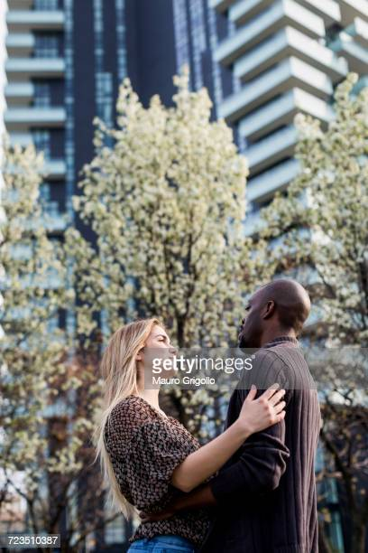 Young couple hugging and gazing at each other in city