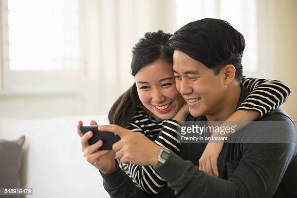 young couple hugging and looking at phone - heterosexual couple stock pictures, royalty-free photos & images