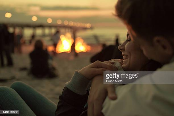 young couple hugging at campfire - utomhuseld bildbanksfoton och bilder