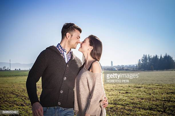Young couple hugging in field