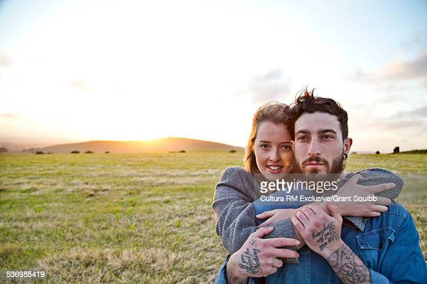 Young couple hugging in rural field, Dorset, England