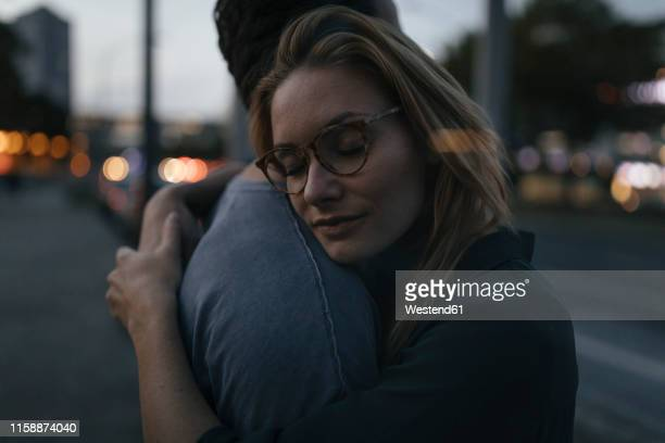 young couple hugging in the city at dusk - umarmen stock-fotos und bilder