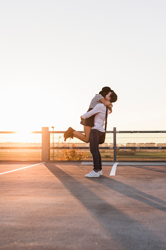 Young couple hugging on parking level at sunset - gettyimageskorea