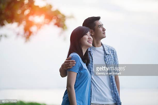 Young couple hugging outdoors,