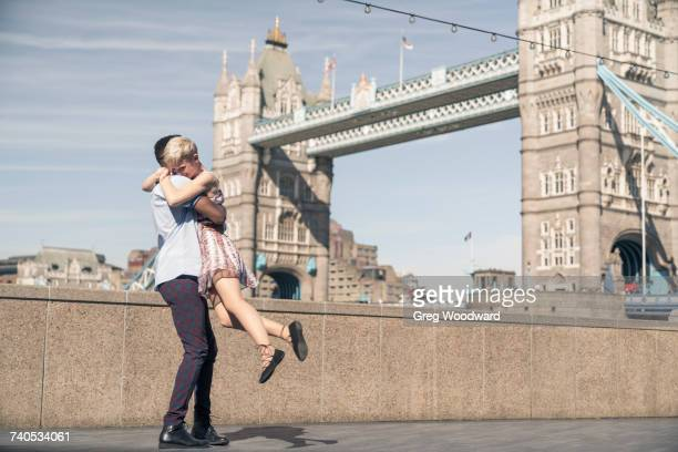 Young couple hugging outdoors, Tower Bridge in background, London, England, UK