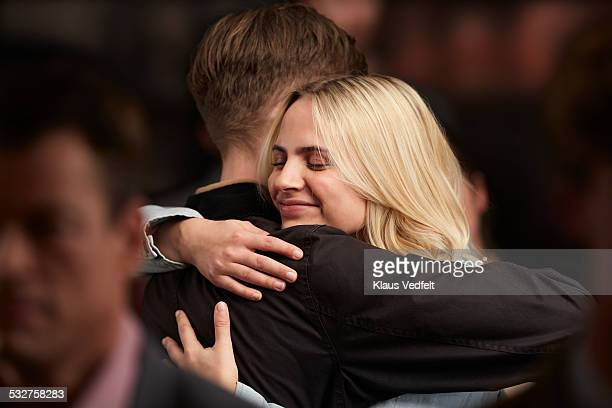 young couple hugging, standing in crowd - wiedersehenstreffen stock-fotos und bilder