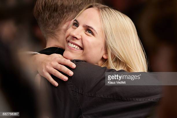 young couple hugging, standing in crowd - boyfriend stock pictures, royalty-free photos & images