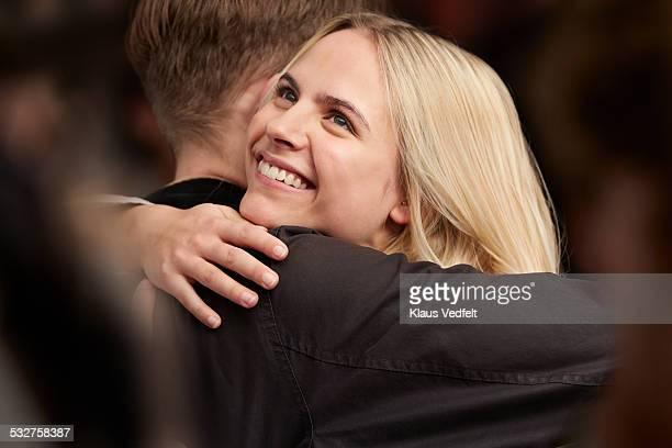 young couple hugging, standing in crowd - vriendje stockfoto's en -beelden