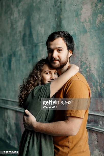 young couple hugging while standing against wall - heteroseksueel koppel stockfoto's en -beelden