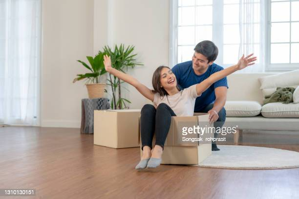 """young couple husband and wife looking happy having fun while unpacking and moving in new appartment. husband carrying his wife in box on the floor""""n - mortgage stock pictures, royalty-free photos & images"""