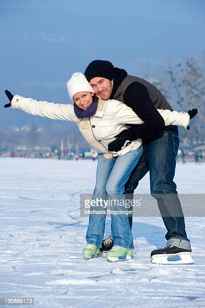 Young couple ice skating on a lake