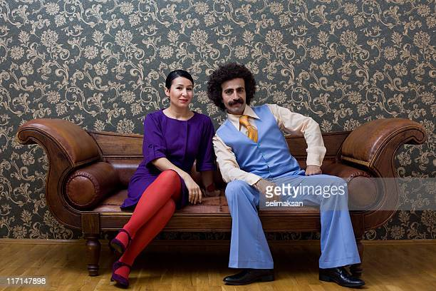Young couple in 1970s style clothings sitting on leather sofa