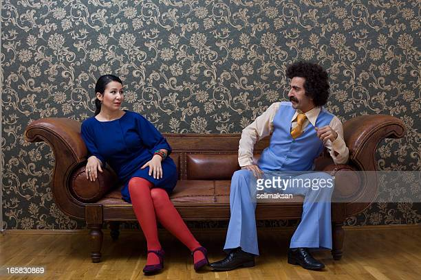Young couple in 1970s style sitting on sofa