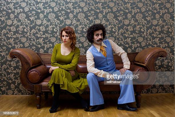 young couple in 1970s style sitting on sofa - mid adult stock pictures, royalty-free photos & images