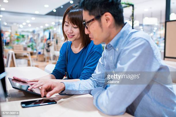 Young couple in a cafe looking at a digital tablet