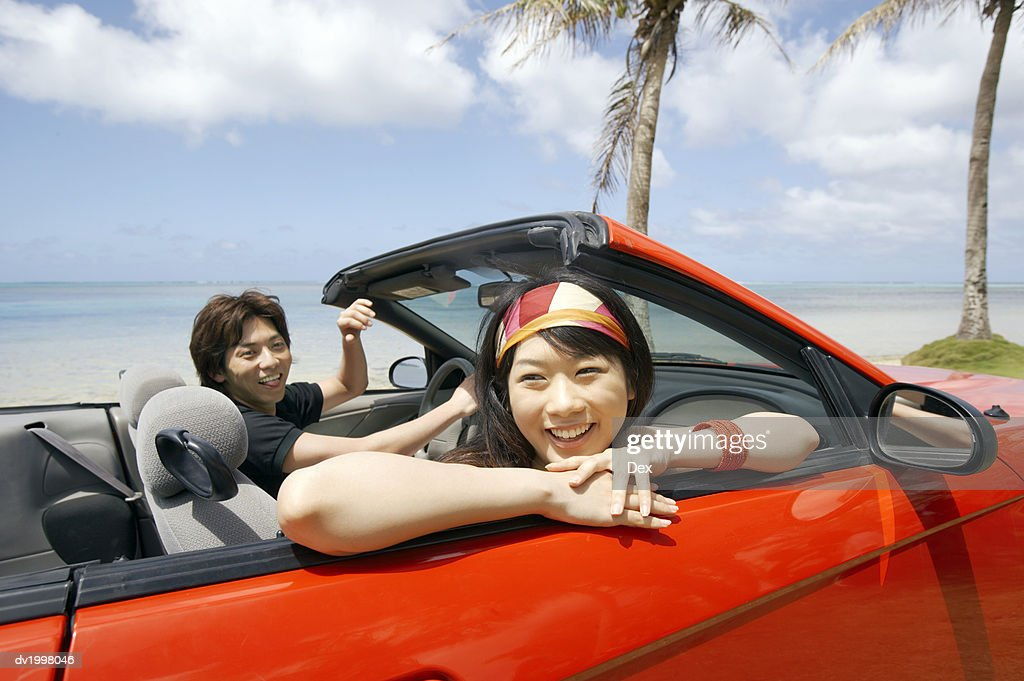 Young Couple in a Convertible by the Beach : Stock Photo