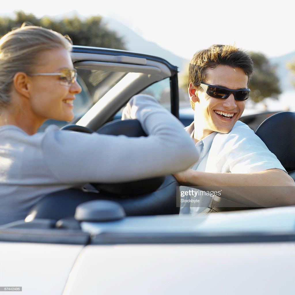 Young Couple In A Convertible Car Wearing Sunglasses High