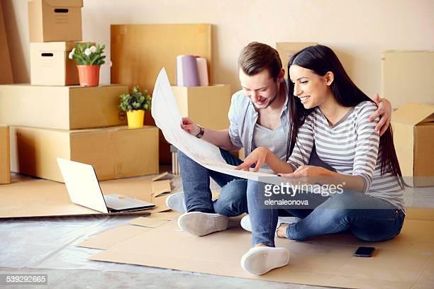 Jeune couple dans un nouvel appartement avec boîtes pour bouger