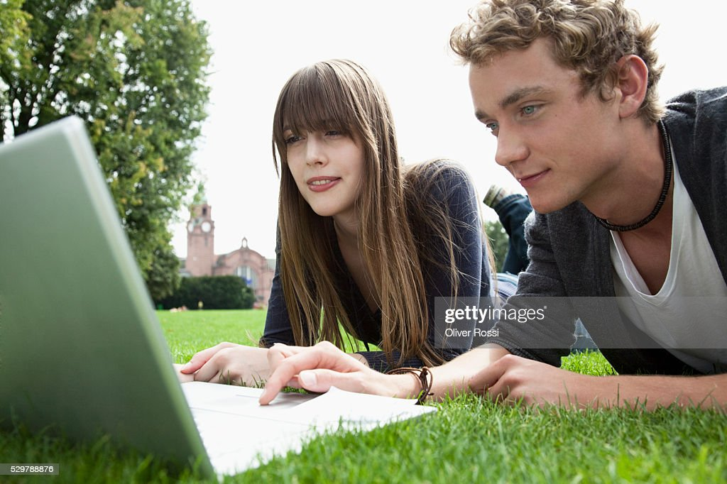 Young couple in a park using a laptop : Foto de stock