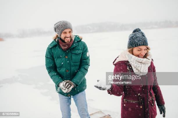 Young couple in a snowball fight