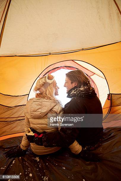 young couple in a tent on winter holiday