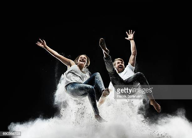 young couple in air with white powder