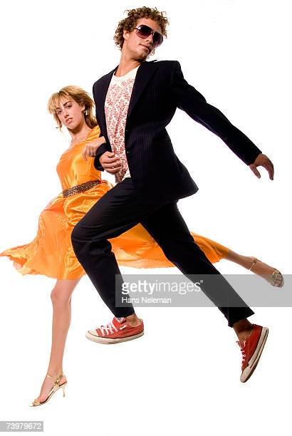 Young couple in alternative evening wear skipping in air