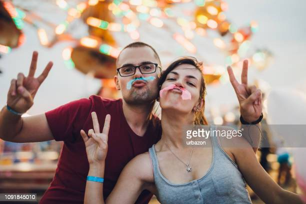 young couple in amusement park - cotton candy stock pictures, royalty-free photos & images