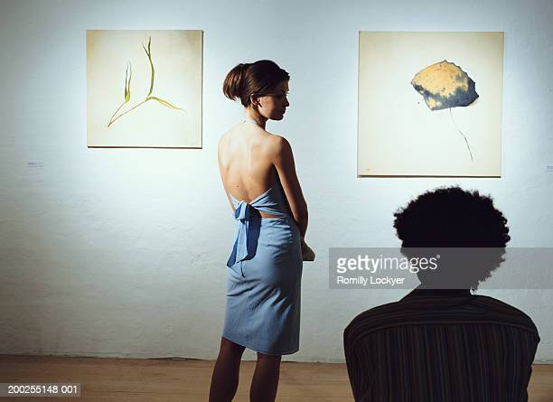 Young couple in art gallery, man sitting, woman standing, rear view