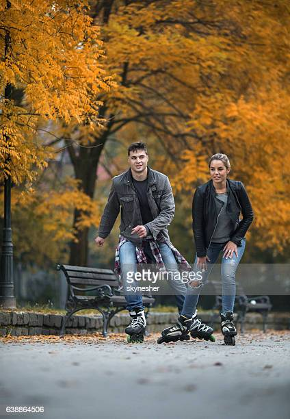 Young couple in autumn park roller skating together.