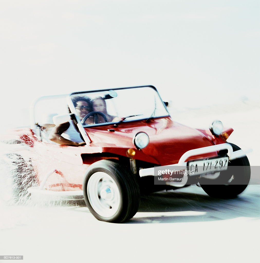 Young couple in beach buggy driving along beach : Stock Photo