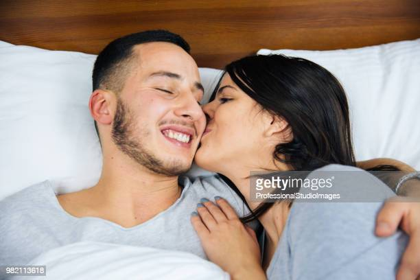Young couple in bed embracing.
