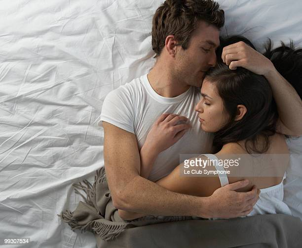 young couple in bed embracing - verhältnis stock-fotos und bilder