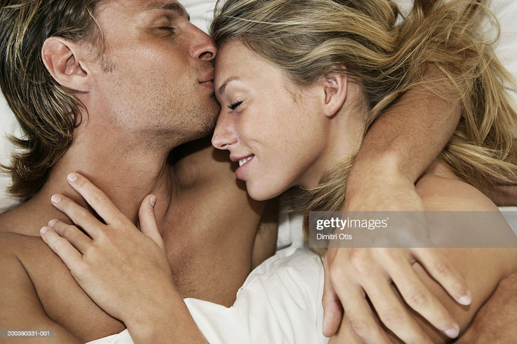 Young couple in bed, man kissing woman's forehead, close-up : ストックフォト