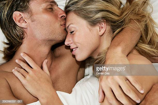 young couple in bed, man kissing woman's forehead, close-up - couple lit photos et images de collection