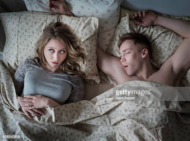 Young couple in bed, man snoring