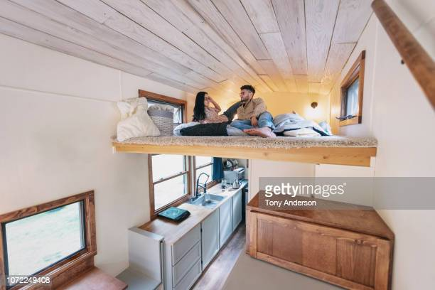 young couple in bedroom loft of tiny house - confined space stock pictures, royalty-free photos & images