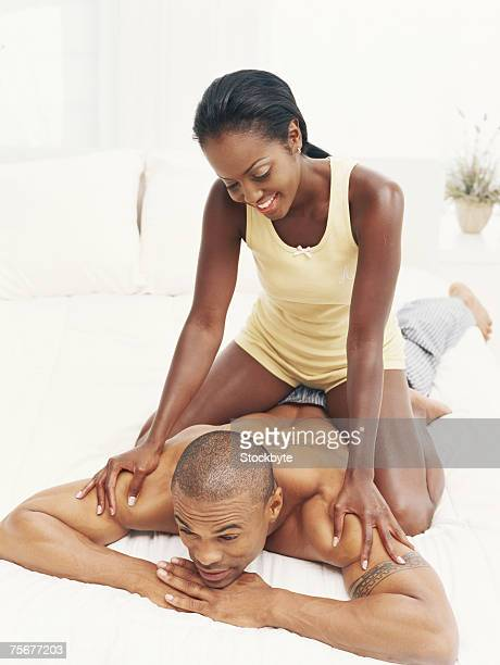 Young couple in bedroom, woman massaging man