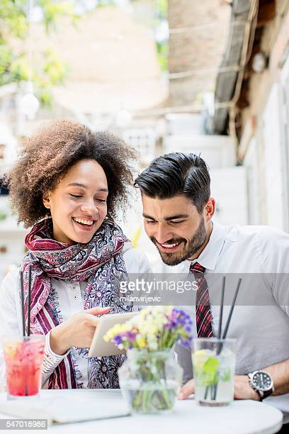 Young couple in cafe bar using tablet