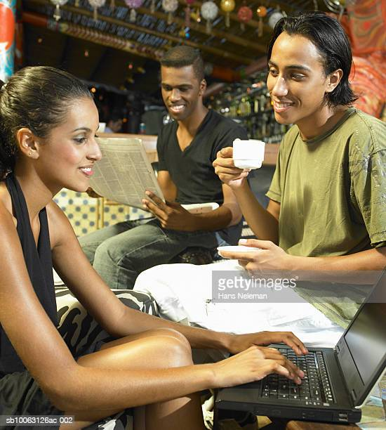 Young couple in cafT, man drinking coffee, woman using laptop