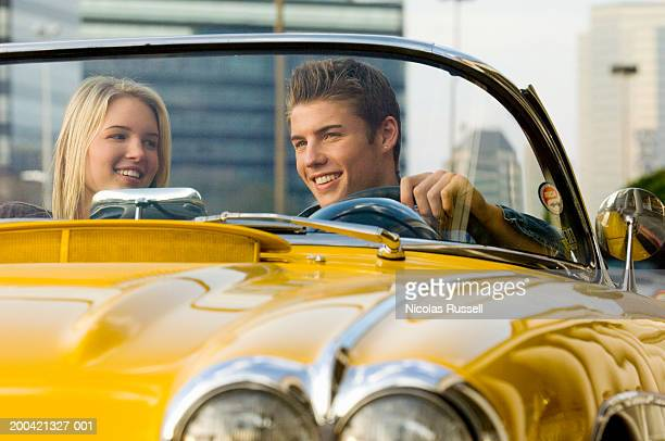 Young couple in car, smiling