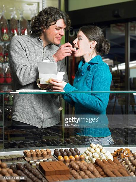 Young couple in chocolate shop, man feeding woman chocolate, smiling