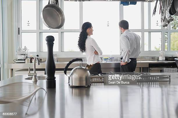Young couple in conversation in kitchen