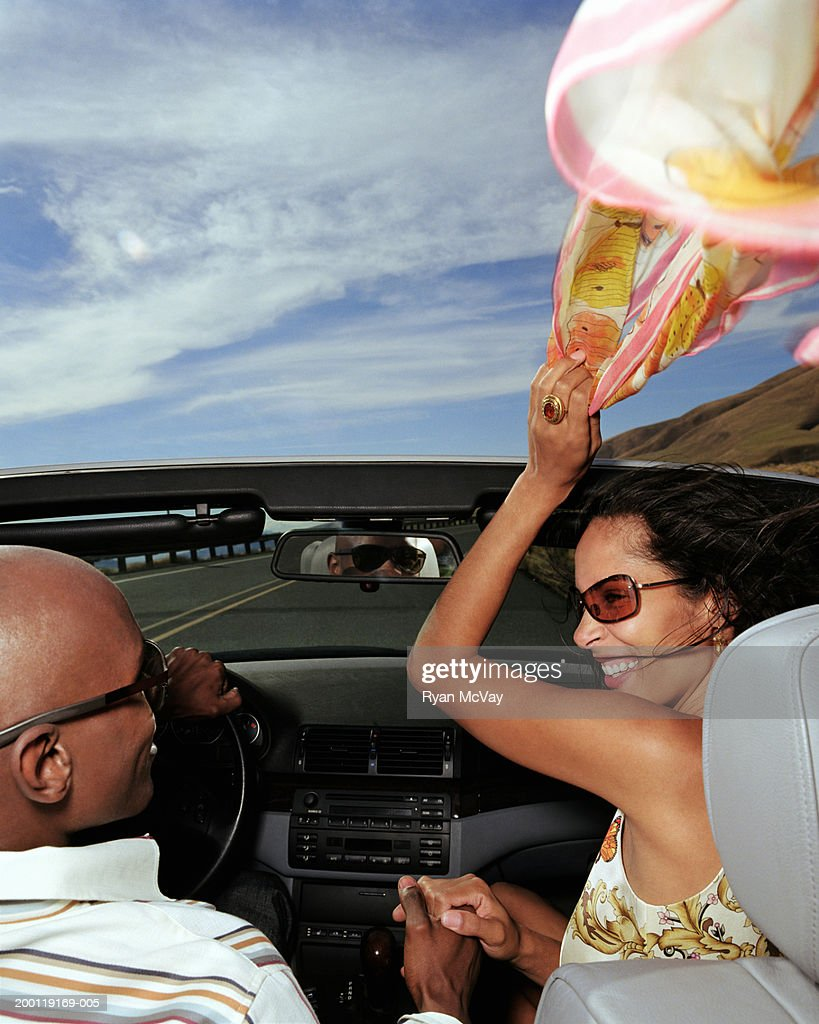Young couple in convertible car, woman holding scarf in wind : Stockfoto