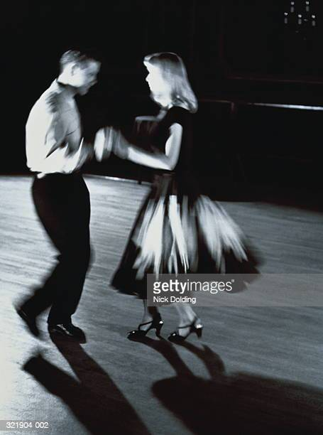 Young couple in costume, dancing together, blurred action