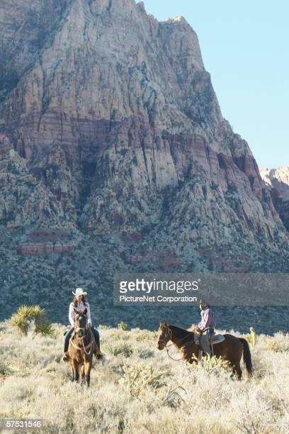 Young couple in cowboy outfits riding a horse