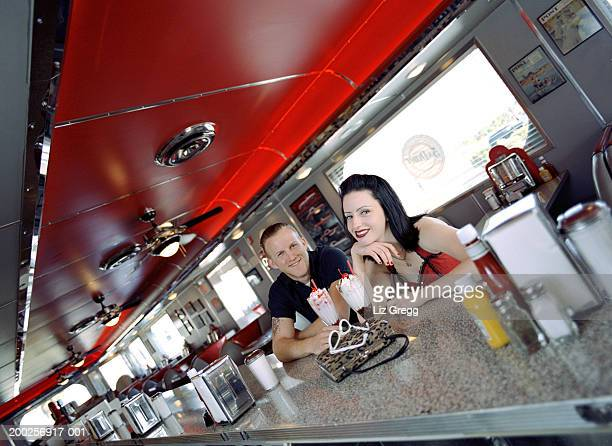 Young couple in diner, smiling, portrait