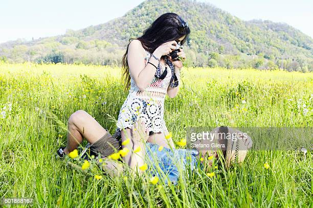 young couple in field, woman photographing man - legs apart stock photos and pictures