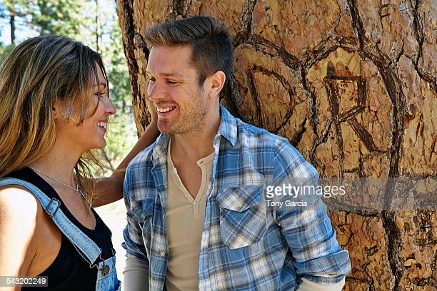 Young couple in forest next to heart carving on tree trunk, Los Angeles, California, USA