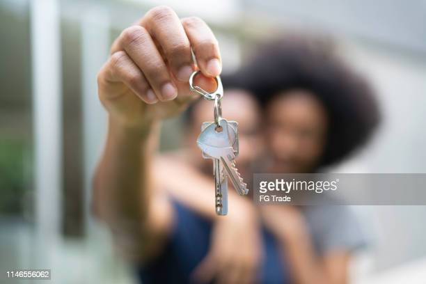young couple in front of a house, holding keys of their new home - home ownership stock pictures, royalty-free photos & images
